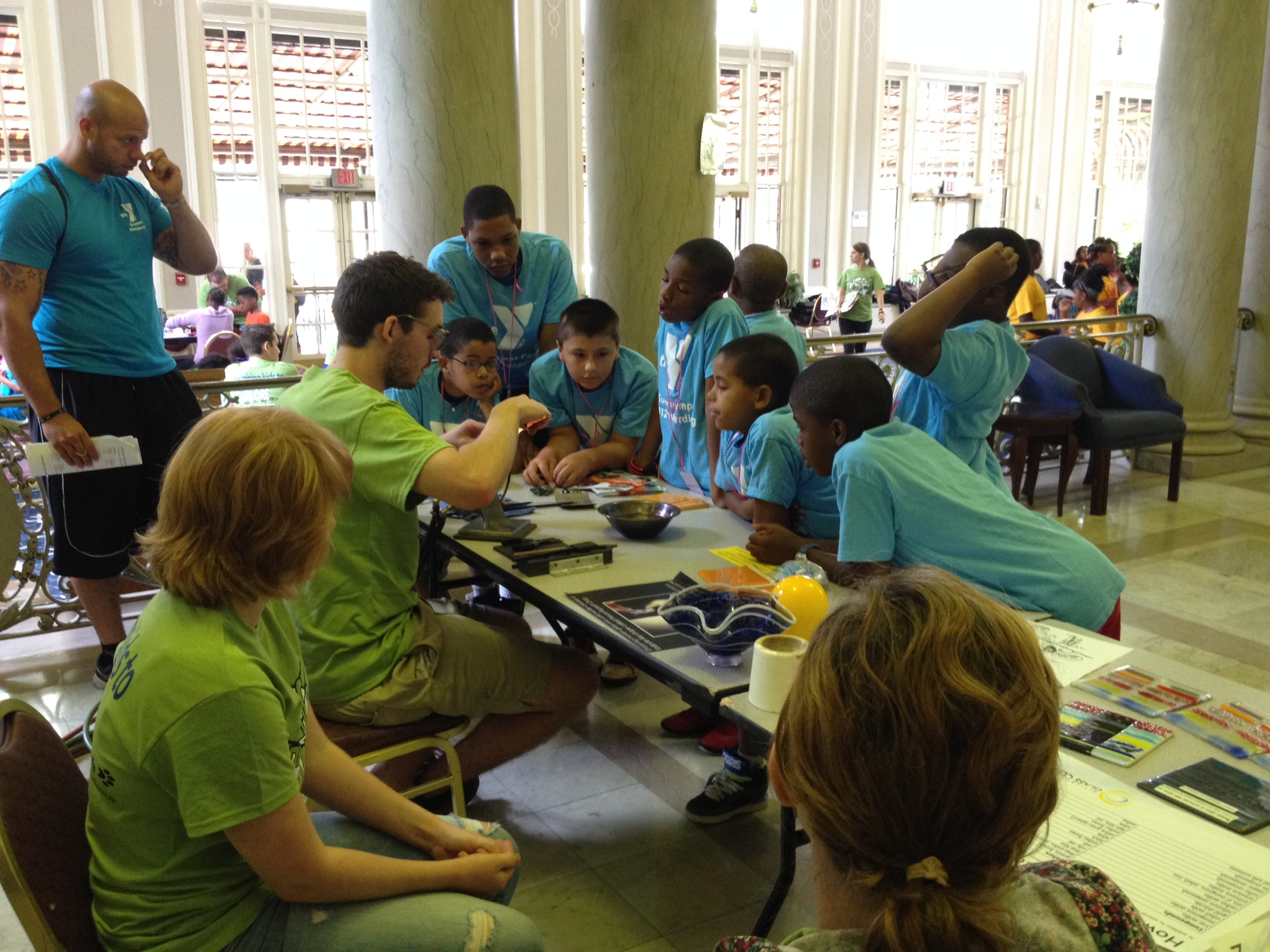 Campers watch in amazement as volunteers teach them about glass blowing.